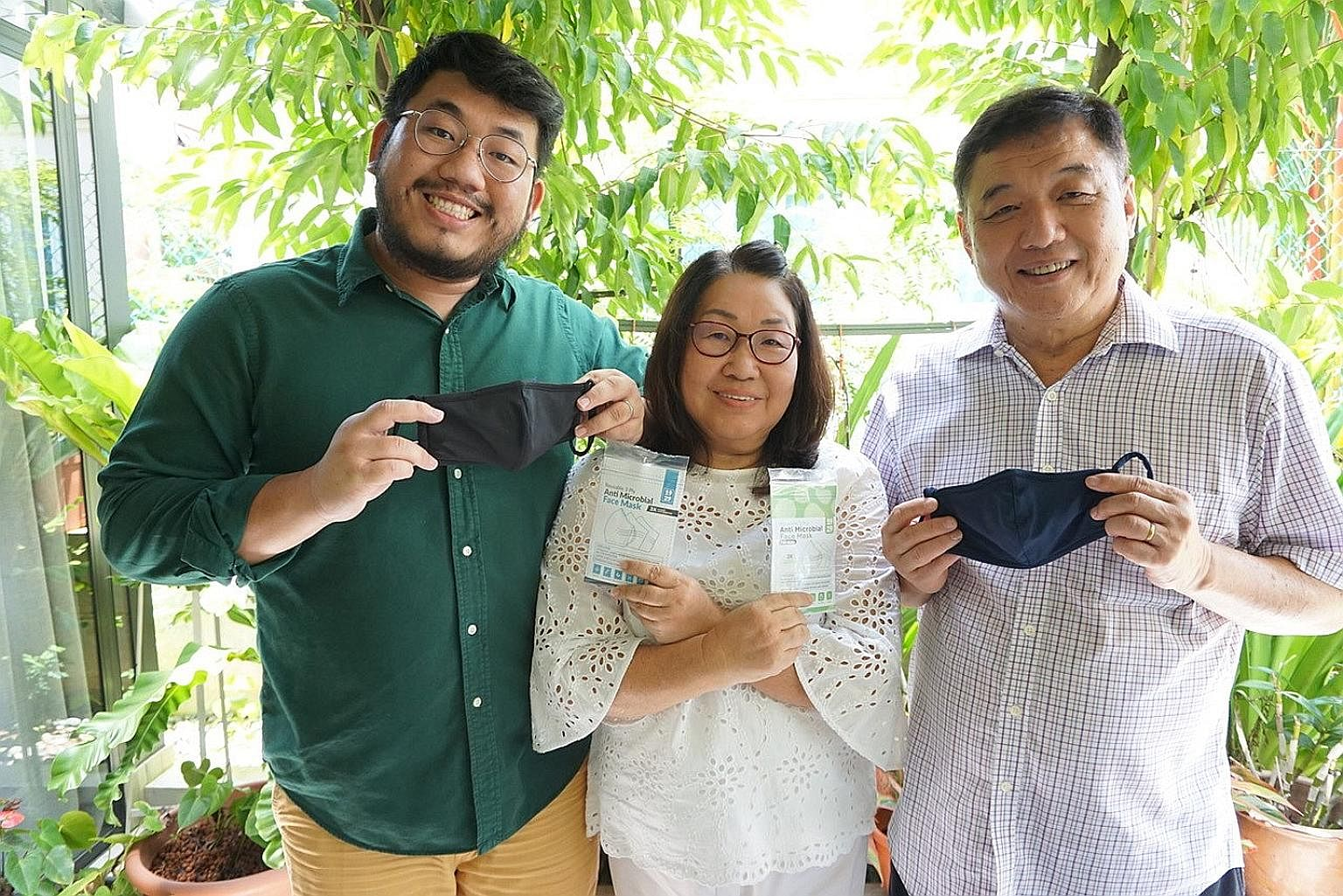 Mr Keenon Lee with his parents, Madam Ng Cheng Choon and Mr Steven Lee. Their family's company, 1929 Mask, makes reusable masks which are also donated to migrant workers and the vulnerable elderly.