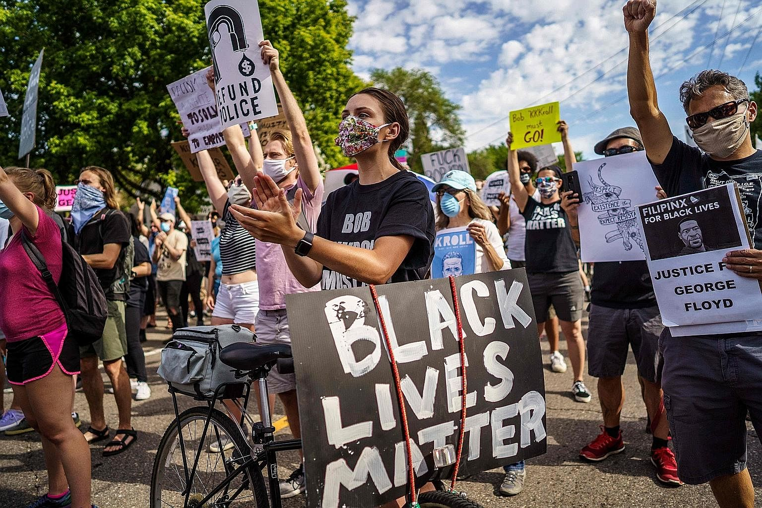 """Protesters outside the Minneapolis Police and Fire Union offices on Friday. As """"Black Lives Matter"""" graffiti and banners appear around the world, and monuments glorifying colonial and Confederate figures are destroyed, institutions in Britain and Ame"""
