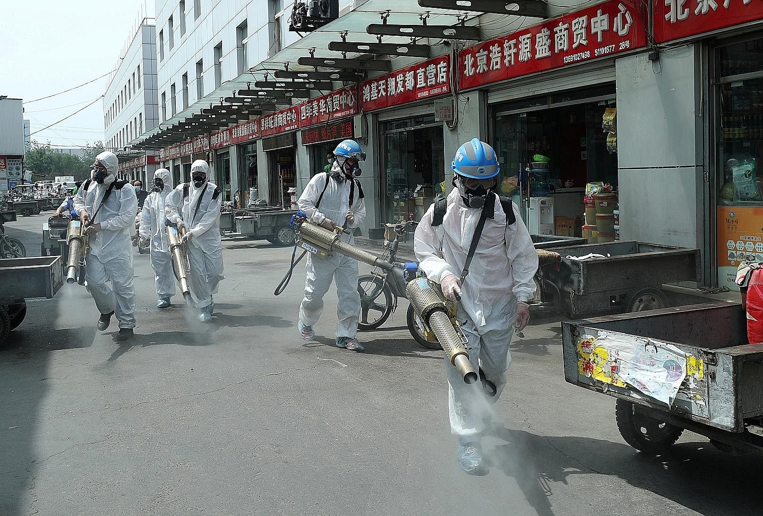 "Volunteers disinfecting Yuegezhuang wholesale market in Beijing on Tuesday. The authorities ordered a disinfection and inspection of all wholesale markets, supermarkets and grocery stores after a market in Fengtai district was labelled a ""hot spot""."