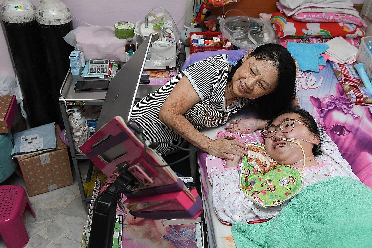 Although she suffers from spinal muscular atrophy type 2 and is confined to her bed, Miss Vivian Goh, seen here with her mother Ivy Yong, is able to run an online business, play online games, watch YouTube videos and attend online church services on