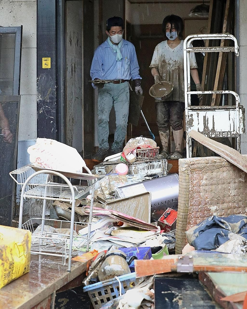 Residents trying to clean up their home damaged by floodwaters due to the torrential rain in Hitoyoshi yesterday. Communities along the Kuma River, which passes through Hitoyoshi, have been hit hard by flooding and over 200,000 people have been urged