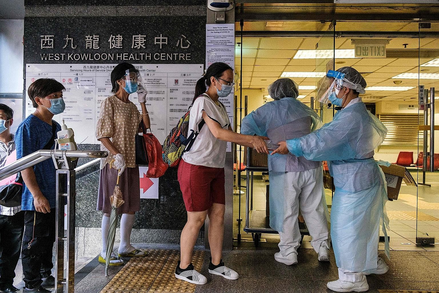 Workers at a government clinic giving out free coronavirus test kits to residents in Hong Kong's Sham Shui Po district early yesterday morning, as part of a citywide testing initiative. Hong Kong's confirmed Covid-19 infections have surpassed the 3,0