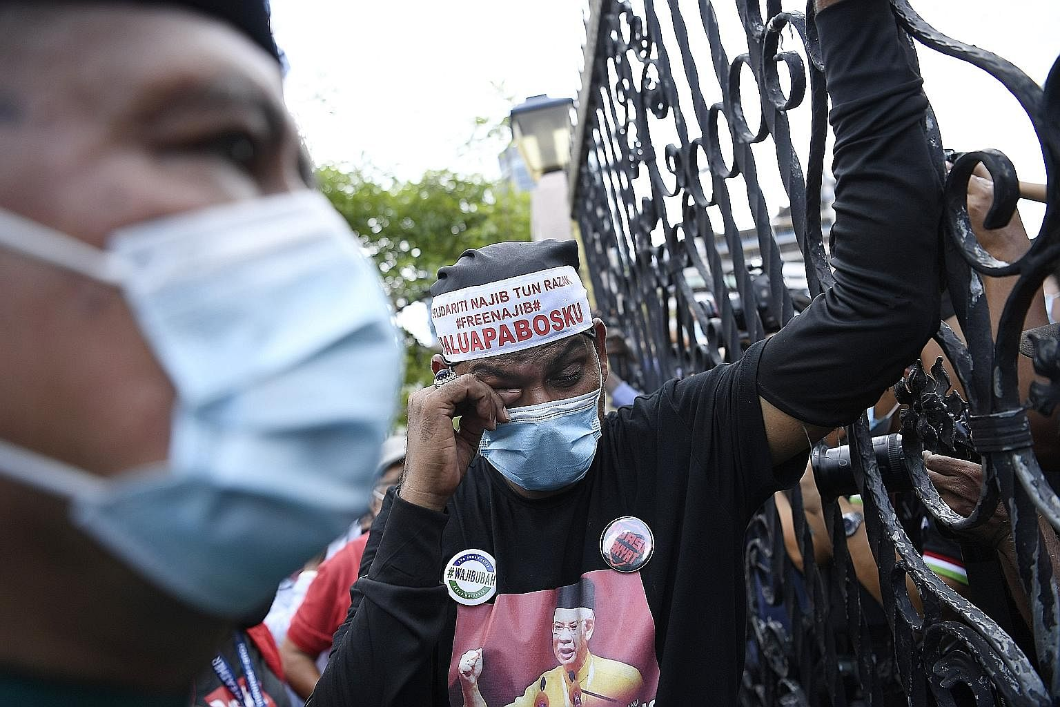 A Najib supporter reacting to the news of the court ruling on Tuesday. Hundreds had crowded the High Court compound to support the former premier. Though Najib still faces another four criminal trials, he remains a popular figure in Malaysia, with hi