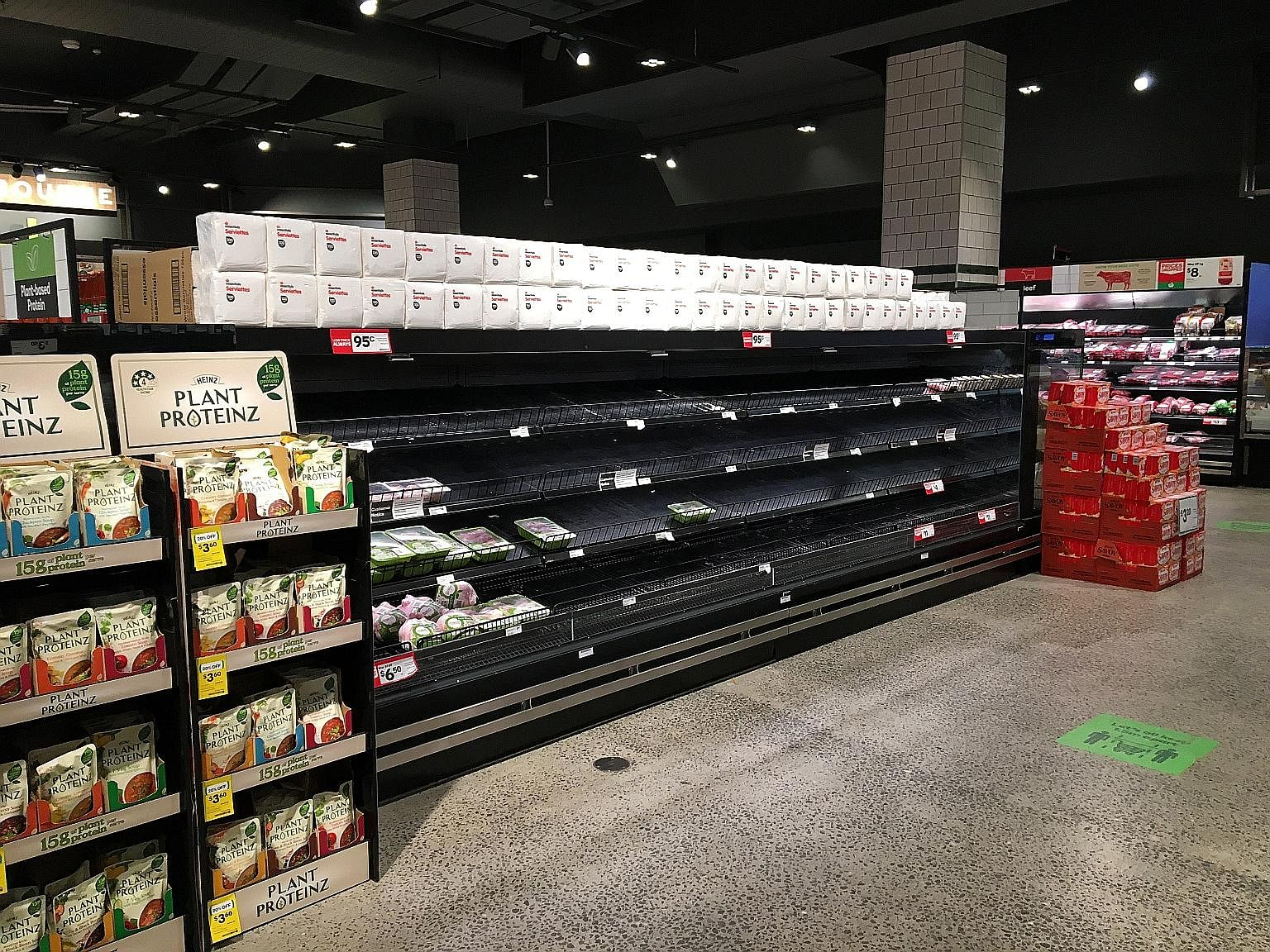 Empty shelves in the poultry section of a Woolworths supermarket (above), and police officers and soldiers patrolling the Treasury Gardens (right) in Melbourne yesterday, as Australia's second-biggest city hunkered down under a strict curfew from 8pm