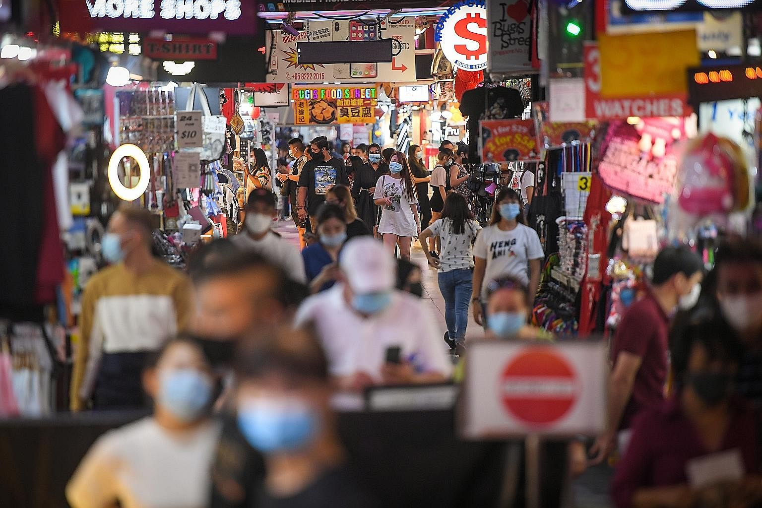 The bustle in Bugis Street on Monday, with the masks on people's faces the only giveaway that Singapore is still battling a pandemic. The currently low infection numbers here and the greater freedom to move around are a reward for everyone working to