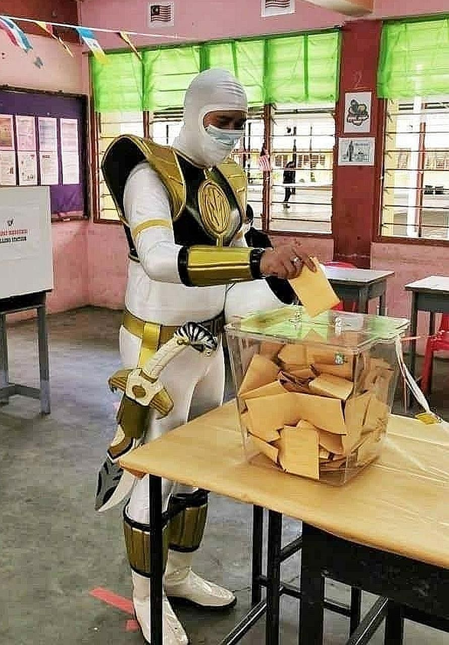 A Malaysian in a Power Ranger costume (above) casting his vote yesterday at the polling centre in SMK Tansau, Penampang, while voters at SRK Sacred Heart (right) in Kota Kinabalu waited to vote. The Sabah election was called after an ally of Prime Mi