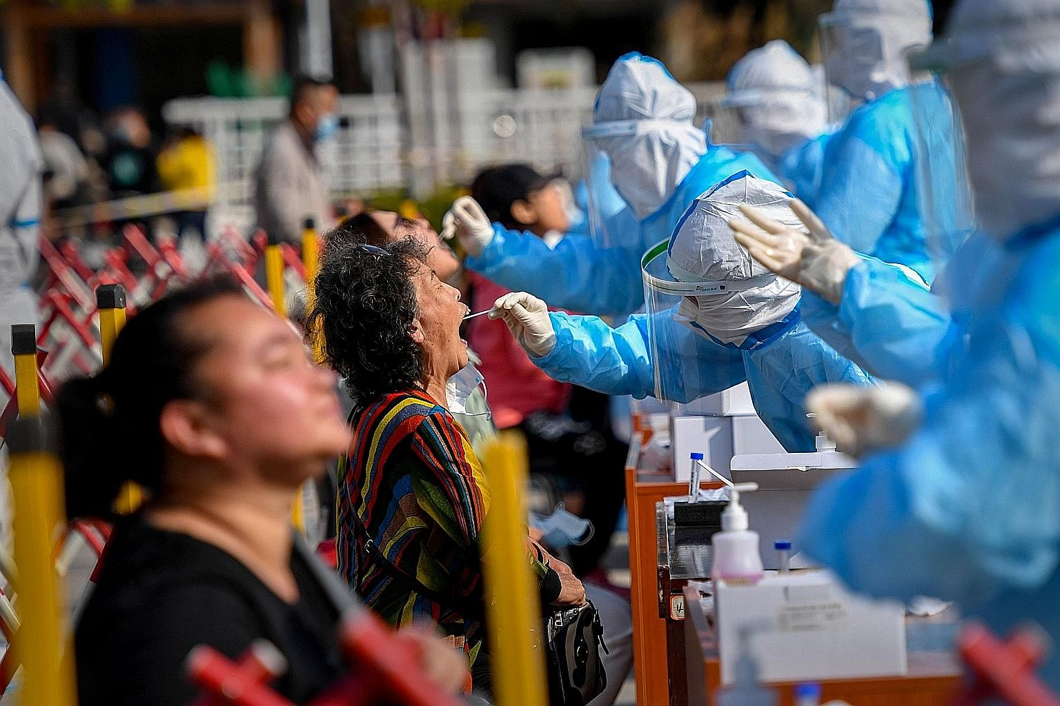 Health workers in Qingdao in eastern China's Shandong province taking swabs from residents for Covid-19 tests yesterday, after the city reported a new cluster of 12 cases, snapping the country's streak of more than two months without a local transmis