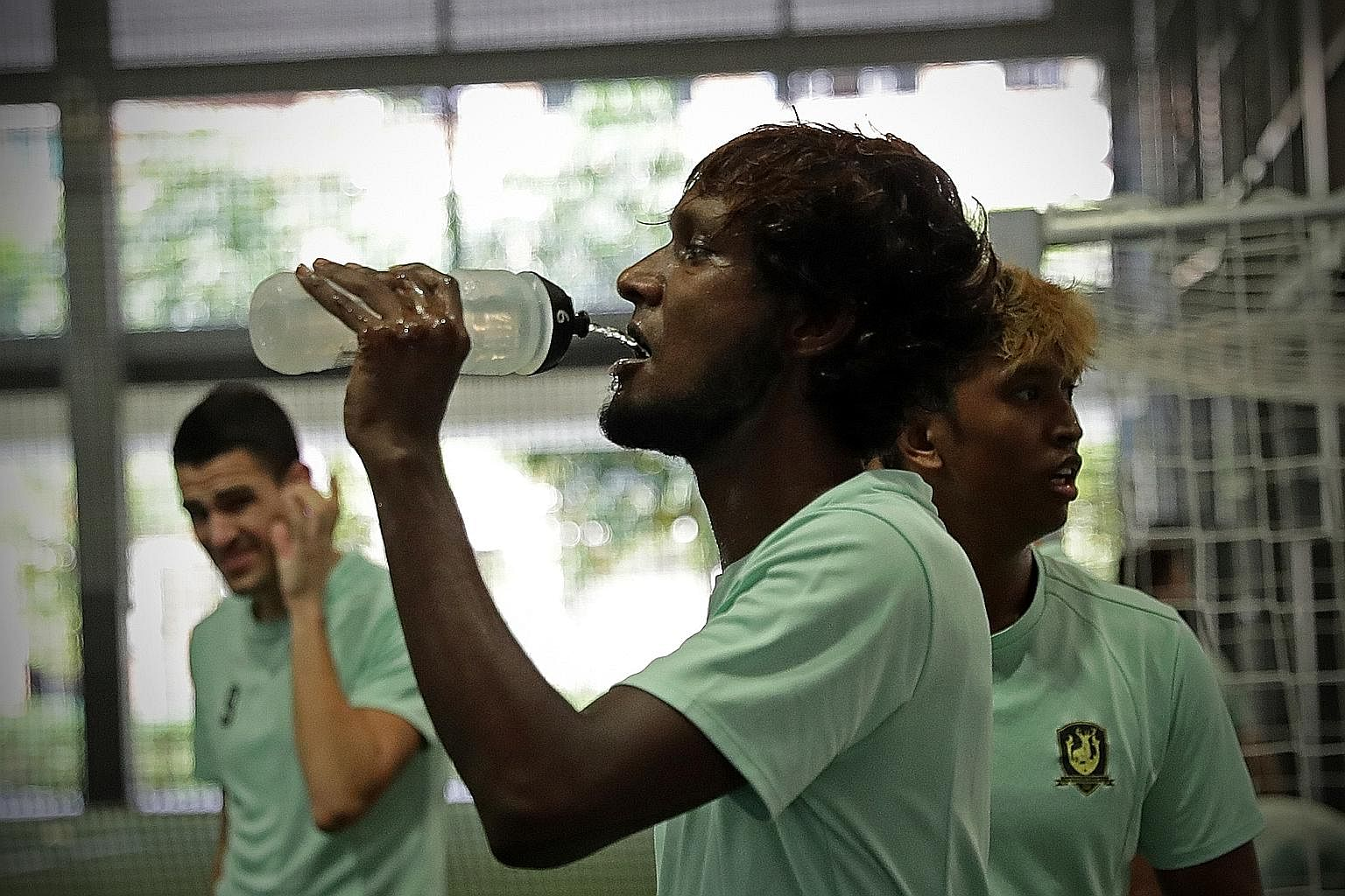 Right, top: Madhu Mohana (centre) drinking from his personalised bottle. Right: The substitutes bench at Bishan Stadium. A temporary amendment to the player substitution rule allows each team to use a maximum of five substitutes. Tampines Rovers kit