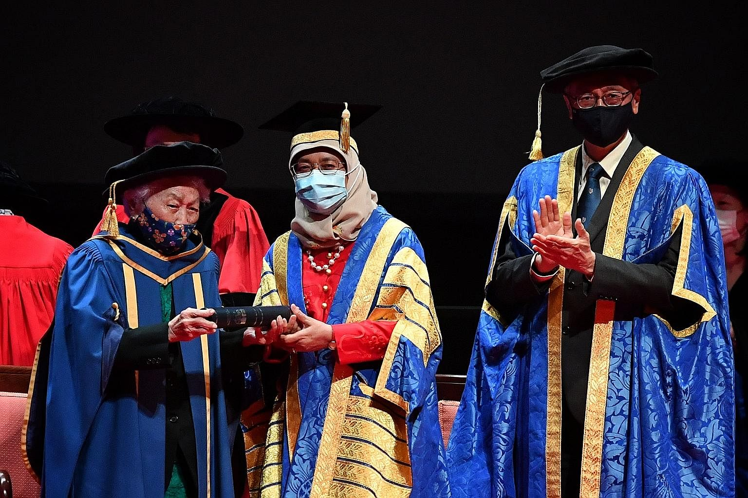Dr Oon Chiew Seng, 104, receiving an honorary National University of Singapore (NUS) degree from President Halimah Yacob, who is also NUS chancellor, at a ceremony held at the University Cultural Centre yesterday. Dr Oon was one of Singapore's first