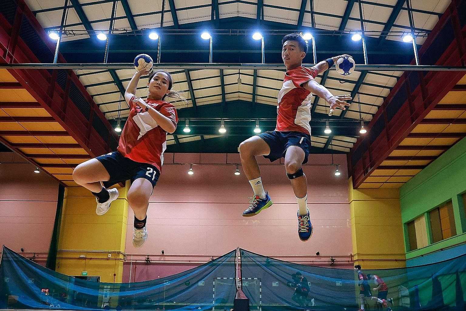 National handballer Ham Jia Yun, 30, and men's captain Teo Kee Chong, 25, showing skill and agility in shooting during training. They have been playing the sport for about 10 years.