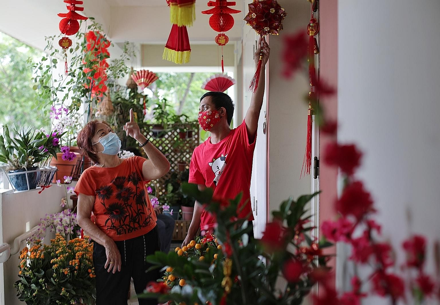 Mr Abdullah Abdul Rahman (right) showing his Chinese New Year decorations to retiree Mary Tay, 70. The resident of the fourth floor of Block 117, Tampines Street 11, put up the festive items and plants to show his appreciation to his elderly neighbou