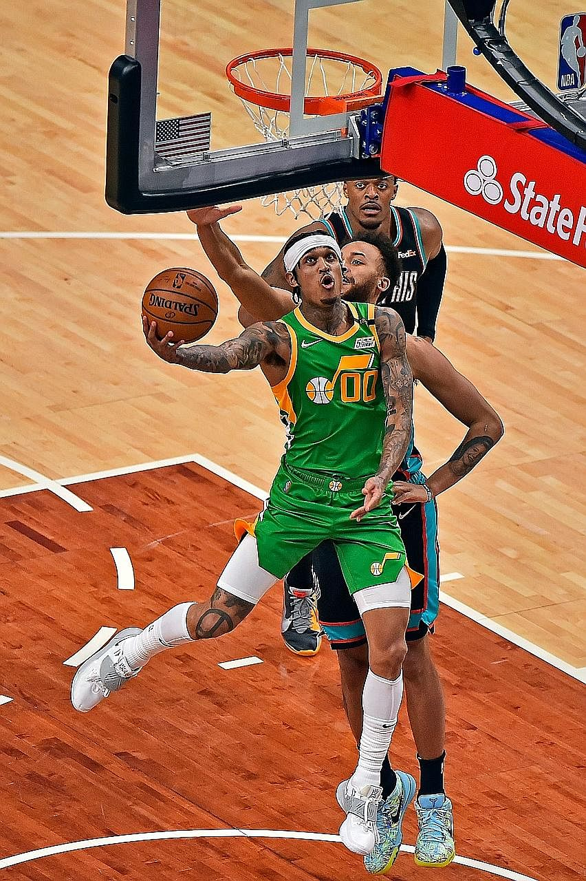 Jordan Clarkson (in green) of the Utah Jazz lays the ball up against the Memphis Grizzlies in their NBA game last Wednesday. The Filipino-American has become a sensation in basketball-mad Philippines.