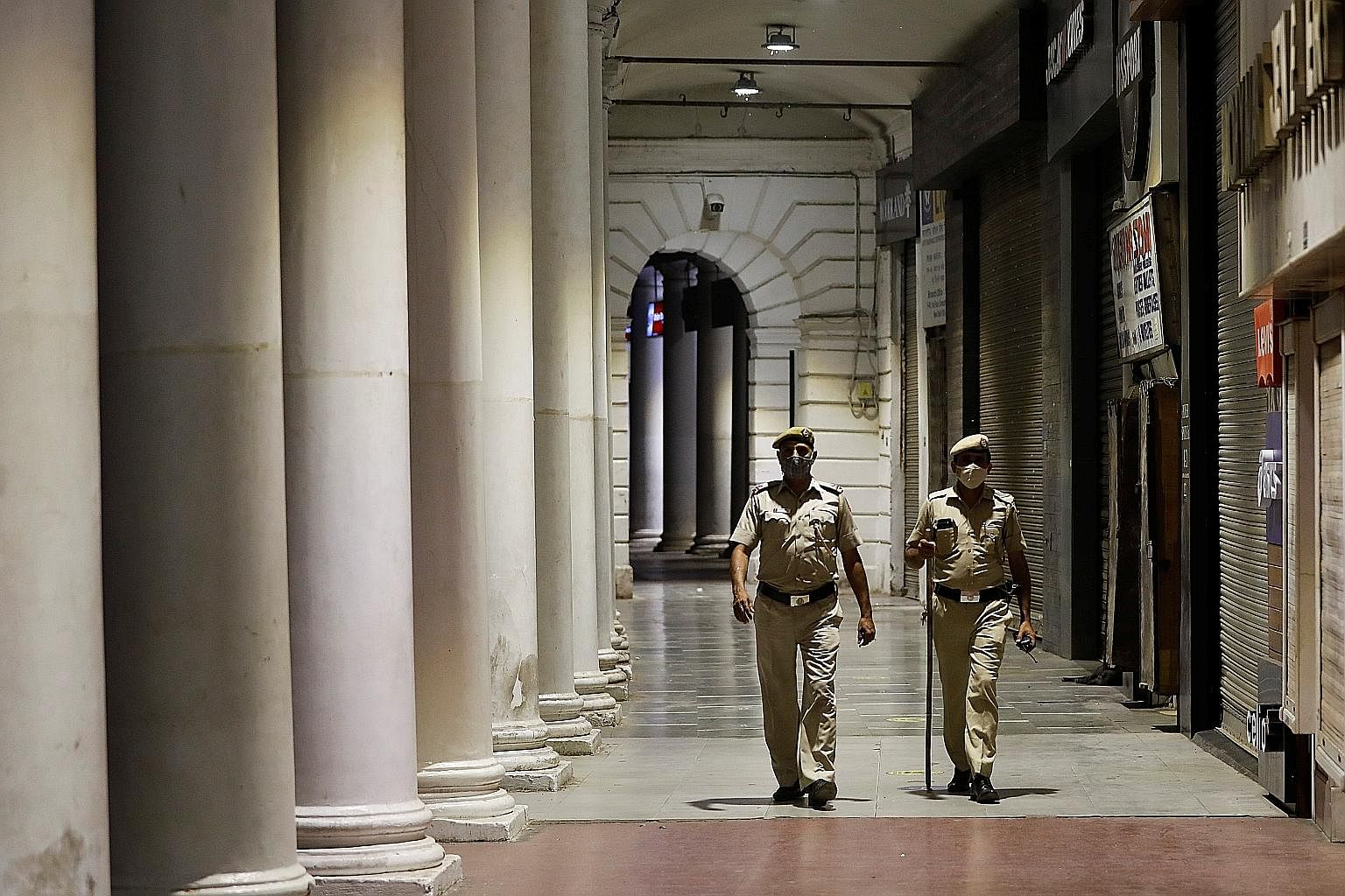 Police patrolling New Delhi's business and financial hub, Connaught Place, yesterday during a curfew. Indian states are imposing new curbs as infections surged to a daily record of 116,000 new Covid-19 cases. Press reports said hospitals were hit, es