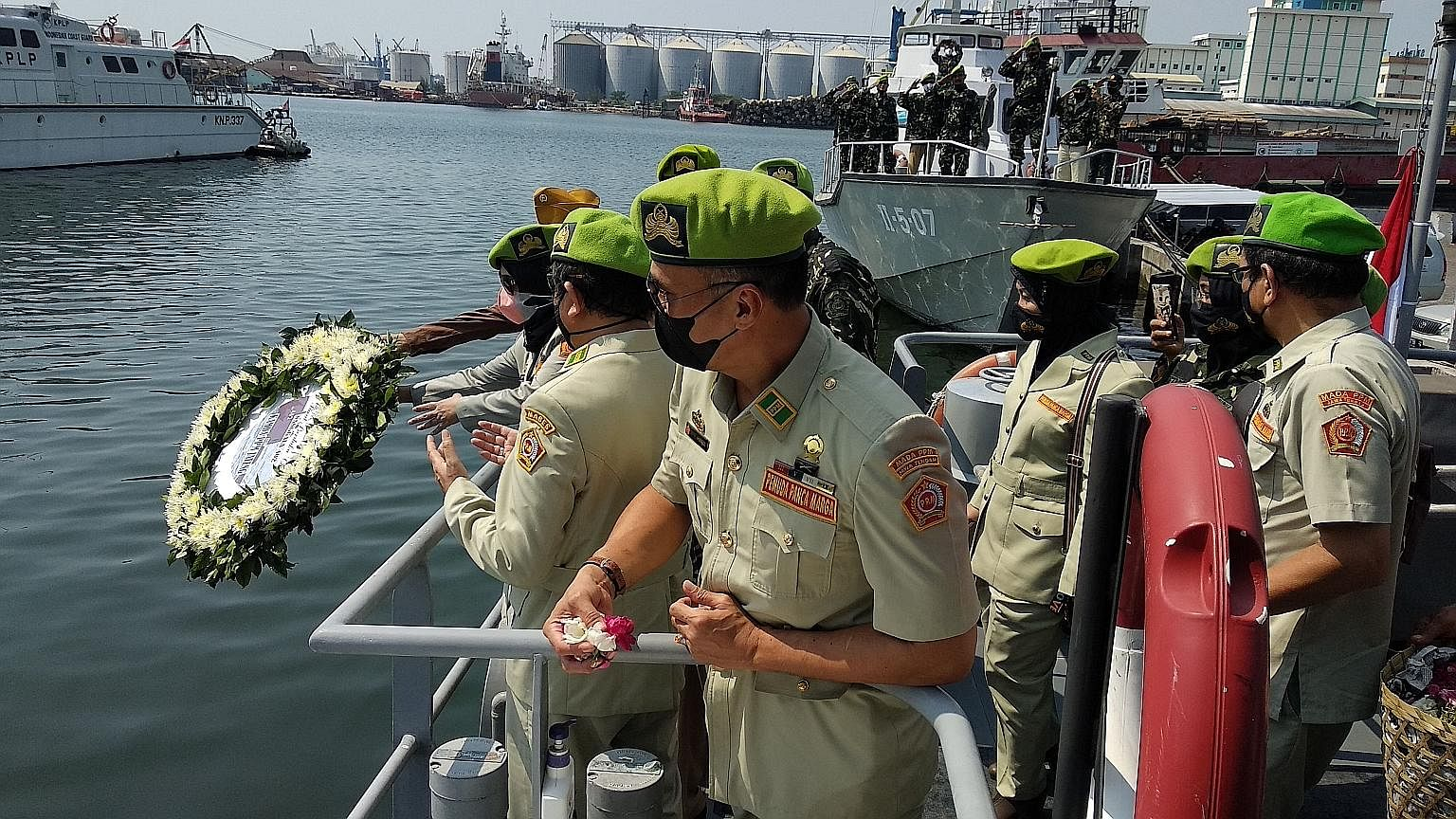 Indonesian naval officers throwing a garland into the sea at Semarang port yesterday as a sign of respect for the 53 crew members who were killed after their submarine sank off the coast of Bali last Wednesday. The navy is now looking at how best to