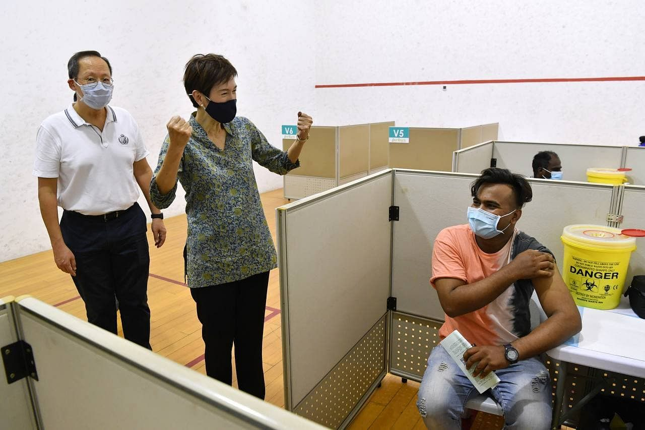 (From left) Second Minister for Manpower Tan See Leng and Minister for ManpowerJosephine Teo share a lighthearted moment with a foreign worker as he receives his Covid-19 vaccination at the Seletar Vaccination Centre on May 2, 2021. ST PHOTO: CHONG JUN LIANG