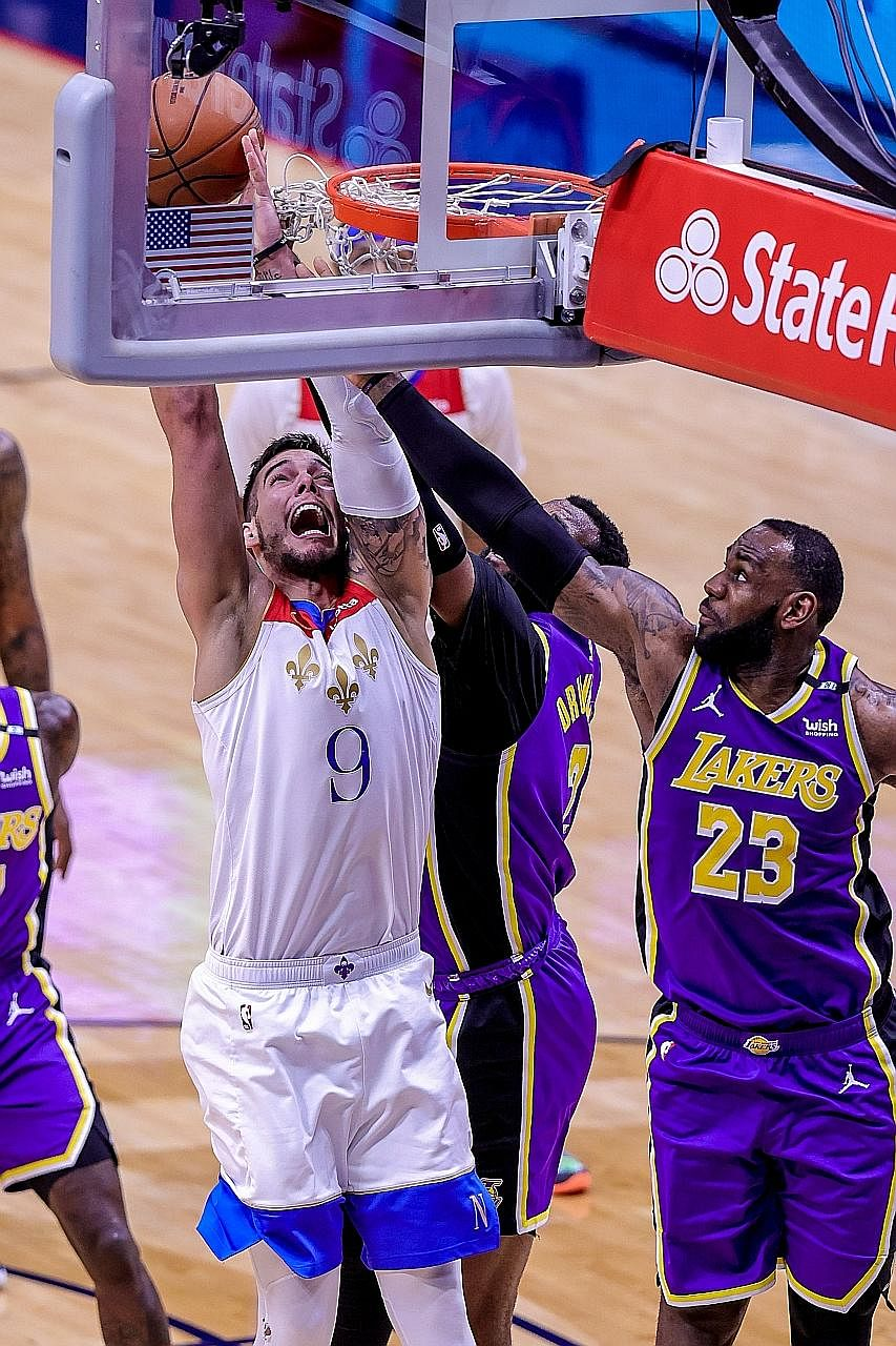 New Orleans Pelicans centre Willy Hernangomez being fouled by the Lakers' LeBron James at the Smoothie King Centre on Sunday. James had a game-high 25 points in their 110-98 win but they could not avoid the play-in.