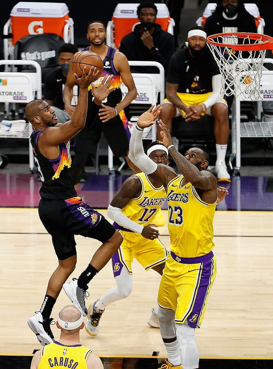 Chris Paul driving to the basket while LeBron James tries to defend. The Suns won 115-85, with Game 6 to be played in Los Angeles.