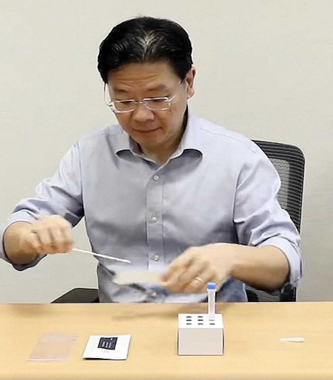 Finance Minister Lawrence Wong trying out a DIY Covid-19 test kit which went on sale in pharmacies yesterday.