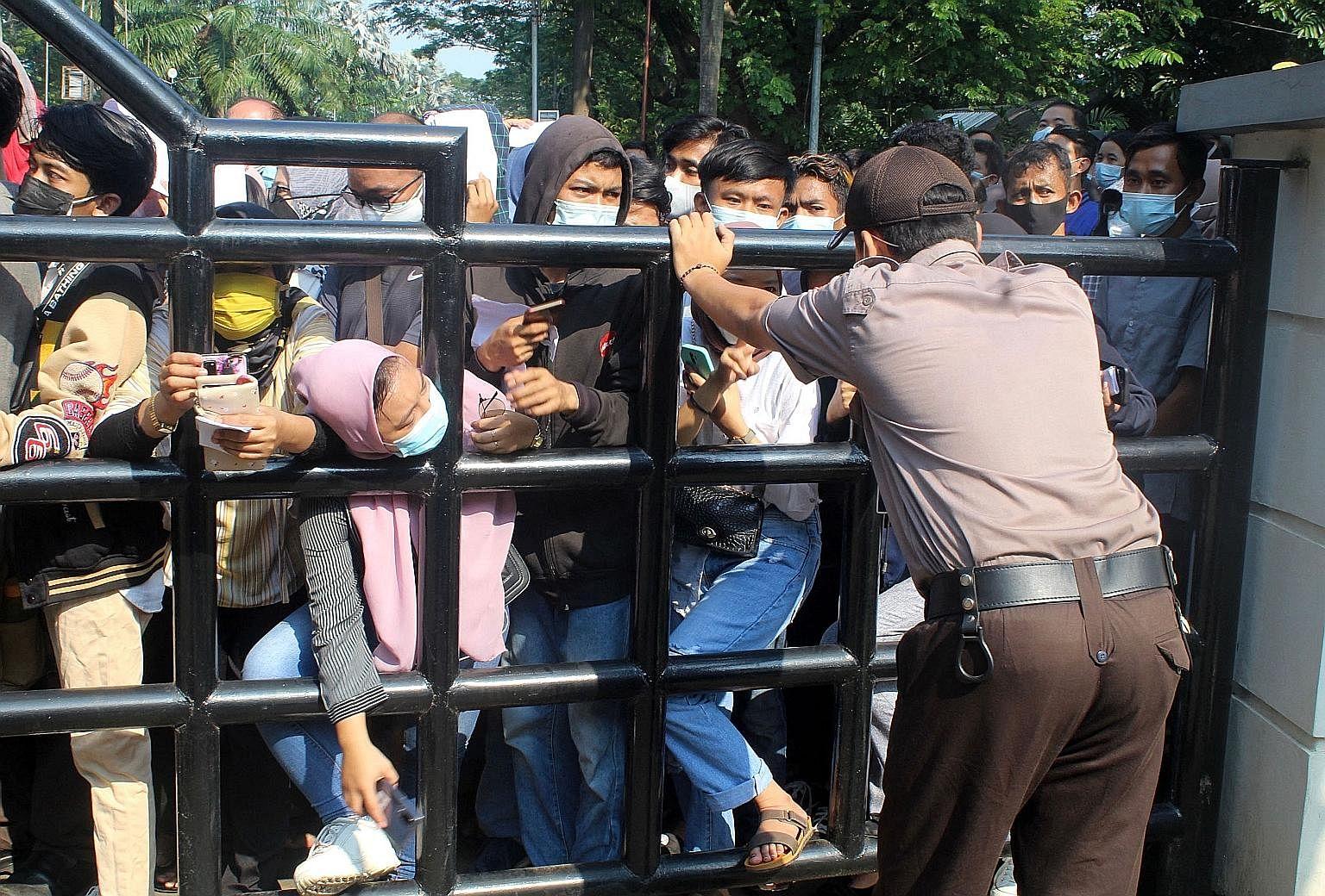 Orang-orang Indonesia berkumpul di luar pusat vaksinasi Pemerintah-19 di Tangerang, pinggiran Jakarta, untuk memerangi epidemi kedua yang didorong oleh keragaman delta yang lebih menular di negara itu.  Indonesia diperkirakan akan memberlakukan aturan yang keras