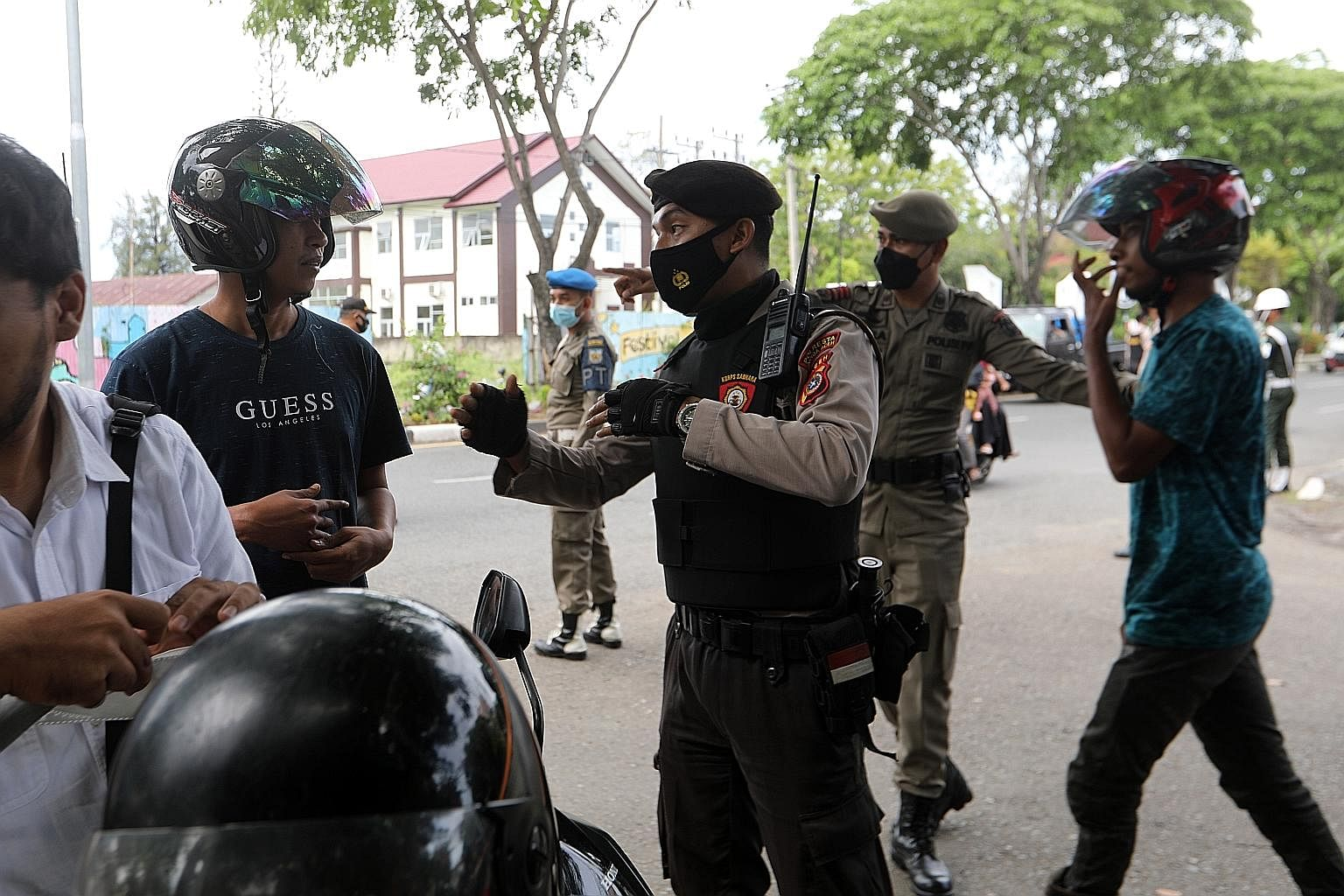 Aceh Joint Security Forces officers carrying out a security check and stopping motorists who failed to wear protective masks in public, in Banda Aceh, Indonesia, yesterday. A health worker administering the Sinovac Covid-19 vaccine at a shopping cent