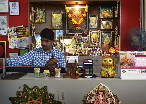 Framed photos of deities are hung behind the cashier counter at Samy's Curry.