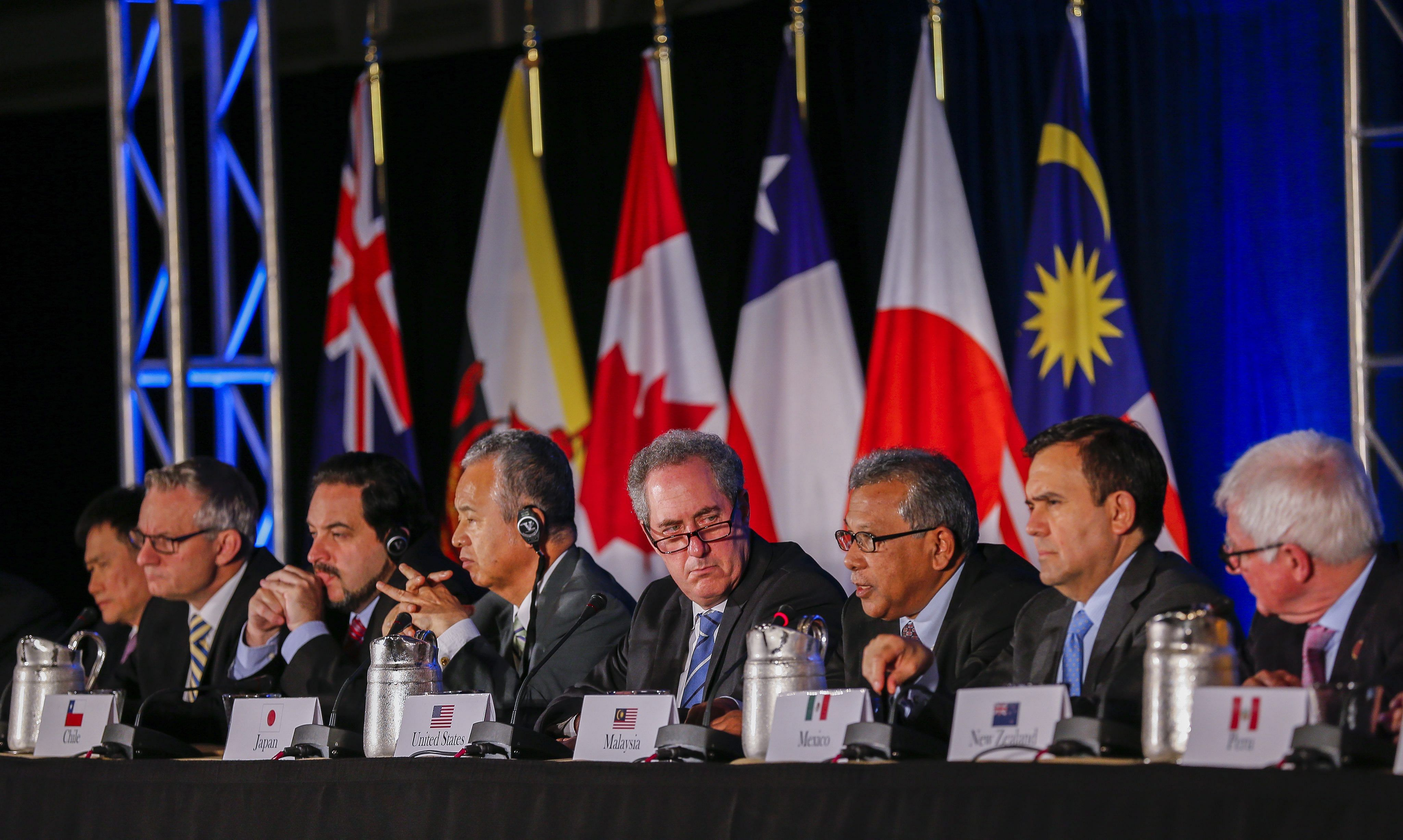United States Trade Representative Michael Froman (centre) being flanked by international counterparts during the closing press conference after an agreement was reached by 12 TPP member countries in Atlanta, in the US, on Oct 5.