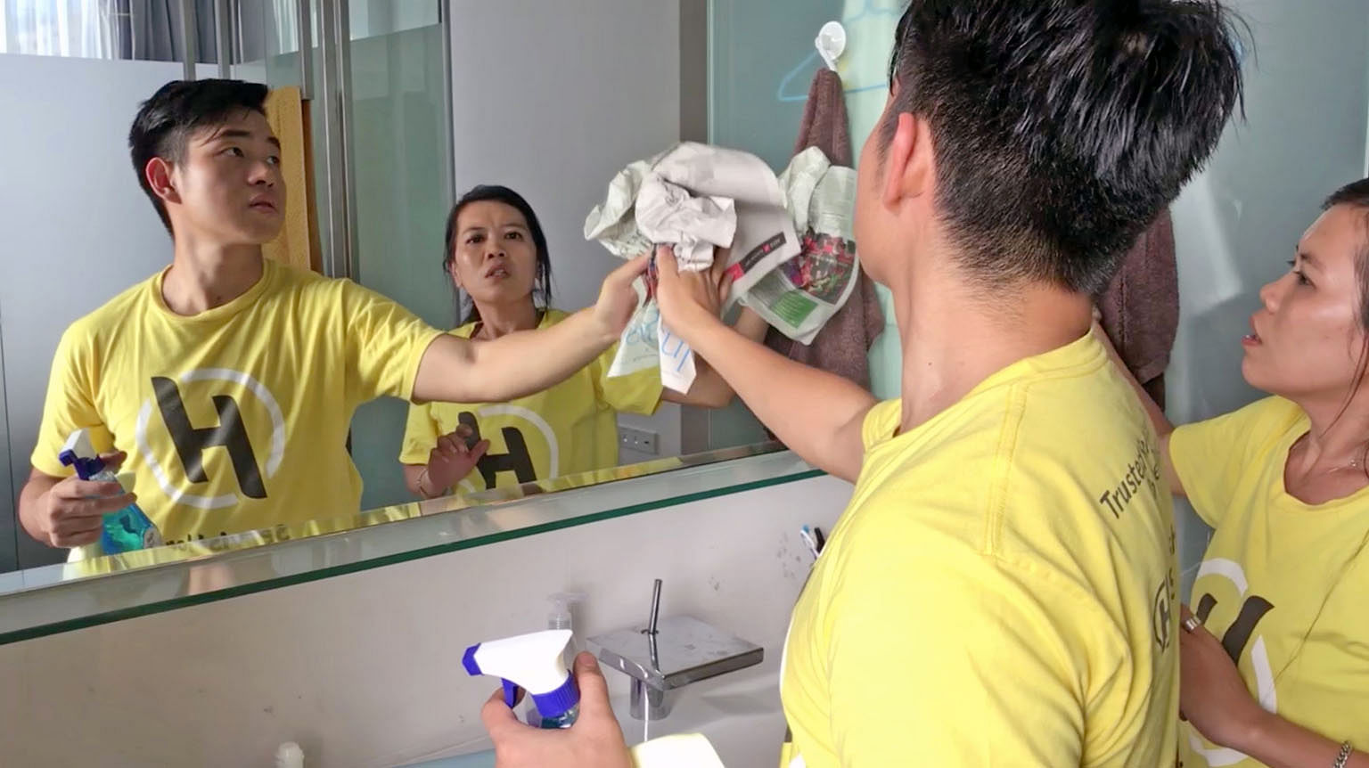 an Asian male and female in a public bathroom cleaning a mirror