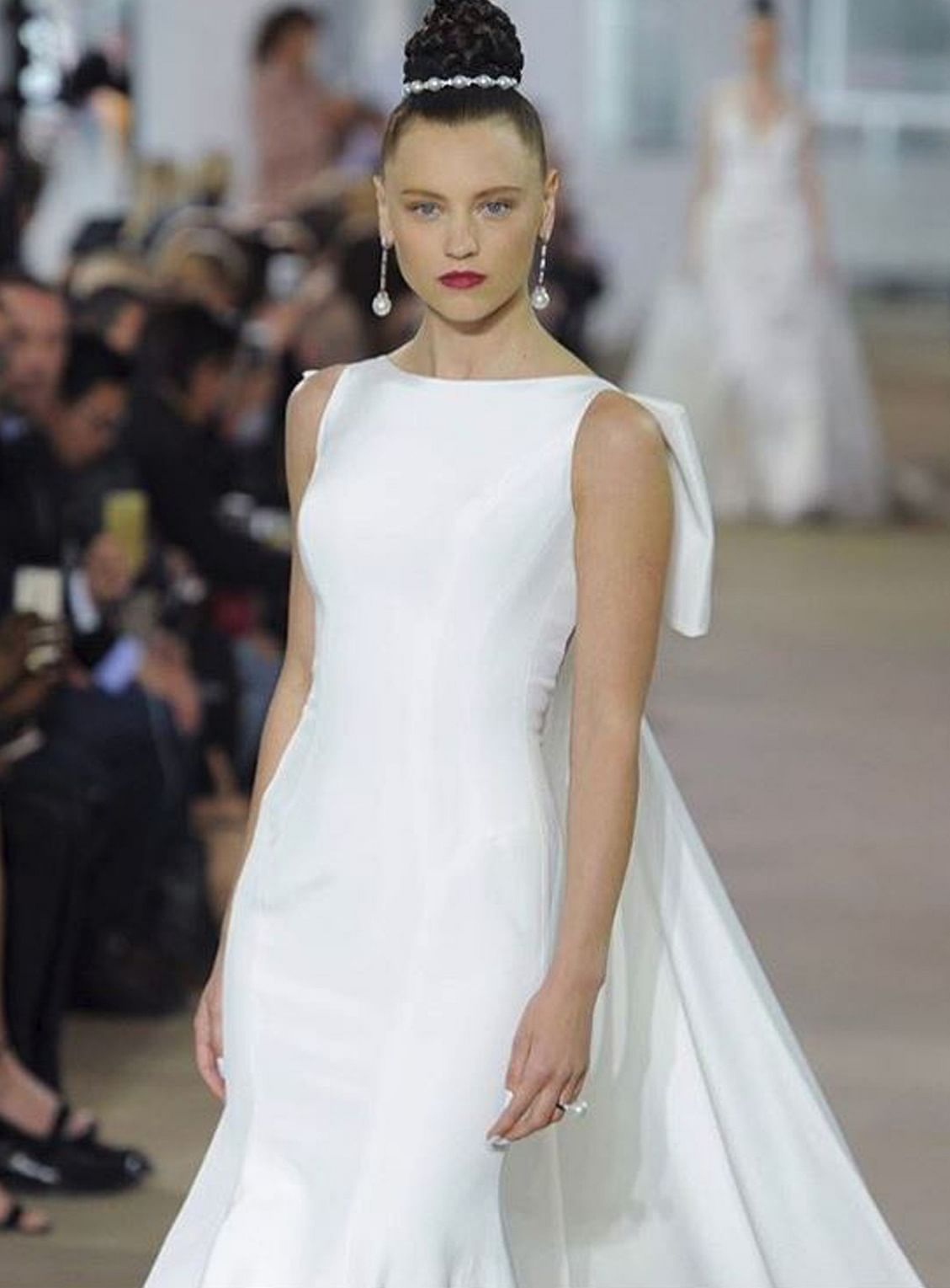 Tuxedo cape with interior sleeves and fitted A-line skirt by Vera Wang. Pared-down, modestly cut bridal gown by Ines Di Santo.