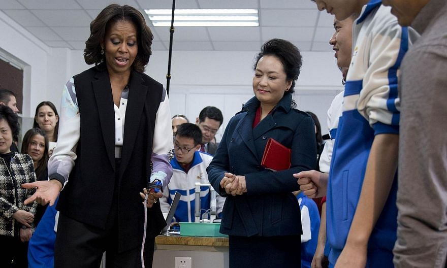 US first lady Michelle Obama (left) tries out a remote-controlled robot next to Peng Liyuan, wife of Chinese President Xi Jinping, during a visit at the Beijing Normal School, a school which prepares students for university abroad, in Beijing, March