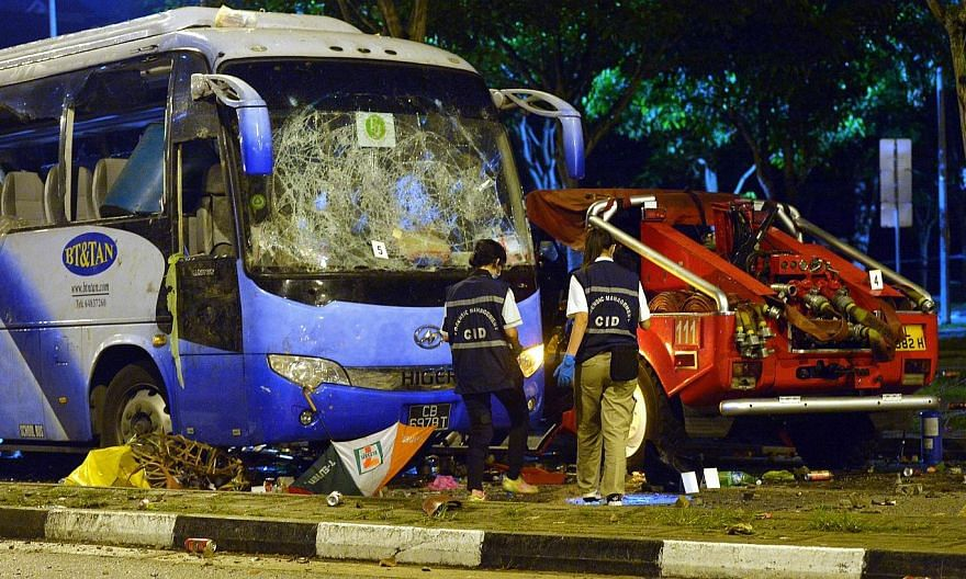 Police officers examining the wrecked private bus at the aftermath of the Little India riot in the early hours on 9 December 2013.The Committee of Inquiry (COI) into last December's riot in Little India found that several misunderstandings abou
