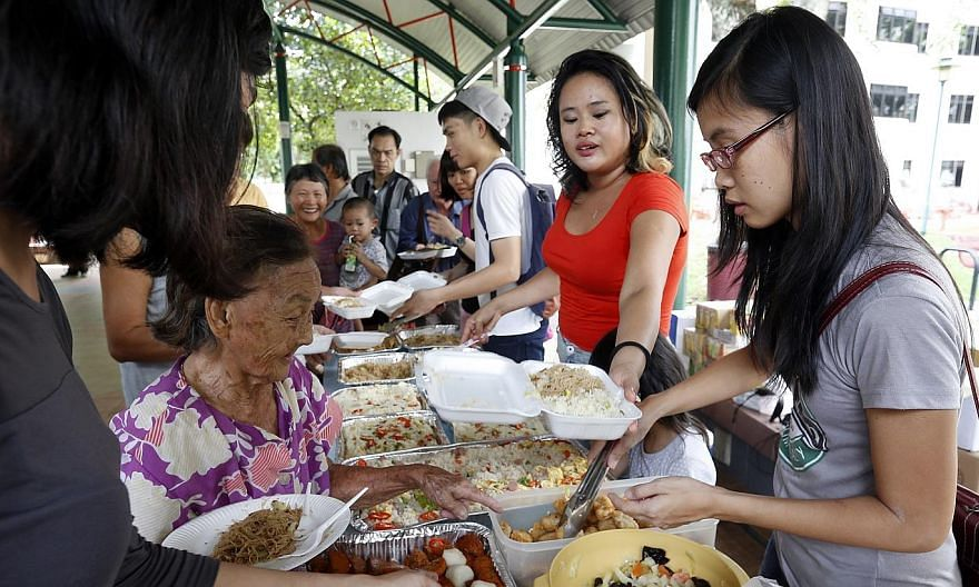 Volunteers help out at a party organised for elderly residents and cardboard collectors by Happy People Helping People Foundation, an informal, non-profit organisation. -- ST PHOTO: LAU FOOK KONG