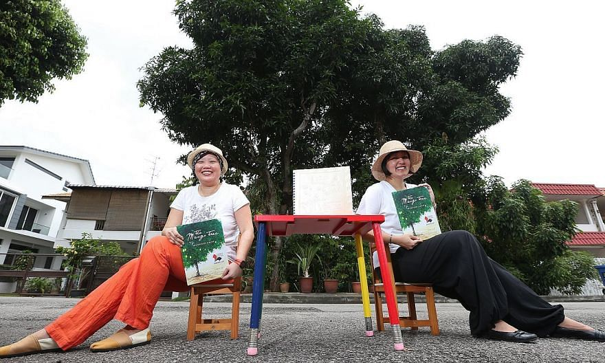 """Local writers Lee Seow Ser (left) and Hidayah Amin, with the Braille and non-Braille versions of Ms Hidayah's The Mango Tree. The Braille version of the 32-page book for children has 10 pages, of which only one has illustrations. """"If we had more mone"""
