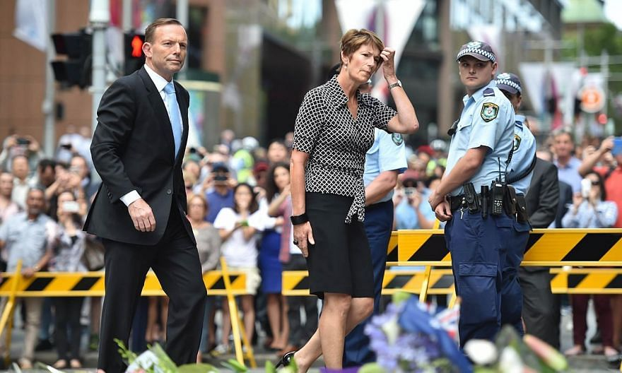 Prime Minister Tony Abbott (left) and his wife Margaret arrive to pay respects and lay wreaths at a makeshift memorial near the scene of a fatal siege in the heart of Sydney's financial district on Dec 16, 2014. -- PHOTO: AFP