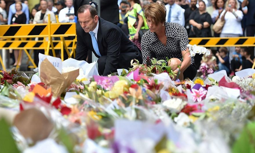 Australian Prime Minister Tony Abbott and his wife Margaret lay wreaths at a makeshift memorial near the scene of a fatal siege in the heart of Sydney's financial district on Dec 16, 2014. -- PHOTO: AFP