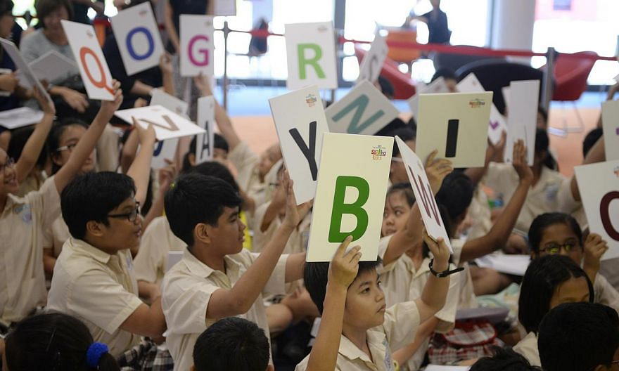 Yishun Primary 5 students hold up cards with letters during a friendly spell-off against Singapore Chinese Girls' School at the launch of the fourth edition of the annual RHB-The Straits Times National Spelling Championship held at Singapore Sports H
