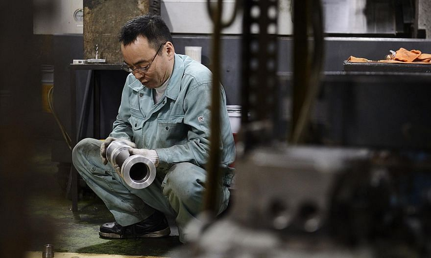 An employee inspecting a machined component at a Kyokuto Seiki Seisakusho K.K. metal machining factory in the Ota ward of Tokyo, Japan, on Dec 5, 2014. -- PHOTO: BLOOMBERG