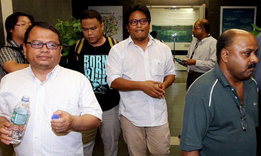(Foreground, from left) The Malaysian Insider's features editor Zulkifli Sulong, Bahasa news editor Amin Shah Iskandar and managing editor Lionel Morais being led out of their office in Mutiara Damansara, Petaling Jaya, on Monday. The three of them w