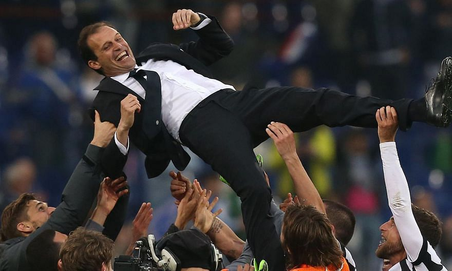 Juventus' players celebrate with their coach Massimiliano Allegri after winningthe Italian title for the 31st time on Saturday. -- PHOTO: AFP