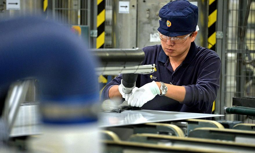 An employee works on solar panels on the module production line at the REC Solar ASA manufacturing facility in Tuas on Sept 5, 2014. Singapore's manufacturing PMI for April will be released on Monday, May 4, 2015. -- PHOTO: ST FILE