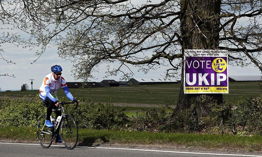 A cyclist riding past a UK Independence Party (UKIP) election campaign poster on the outskirts of Aylesbury, north-west of London, on April 30, 2015. UKIP candidate Robert Blay has been suspended after a video of him insulting Conservative rival Rani