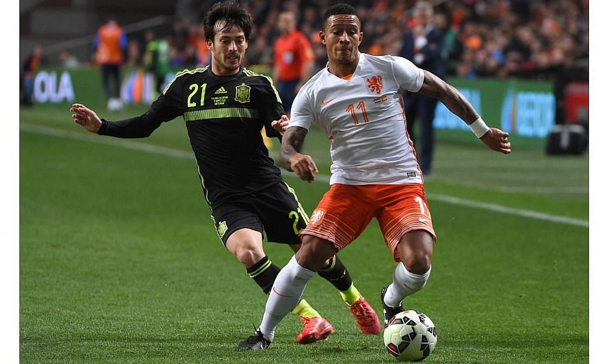 Memphis Depay (right) vies with Spain's David Silva during the friendly football match Netherlands vs Spain in Amsterdam, on March 31, 2015. -- PHOTO: AFP