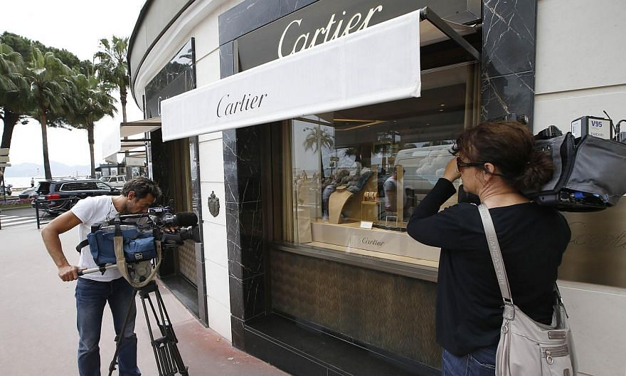 Journalists work in front of the Cartier jewellery shop on the Croisette in Cannes, French Riviera, on May 5, 2015, after the hold up by four armed men who fled with a large amount of jewellery.With France still on high alert after January's attacks