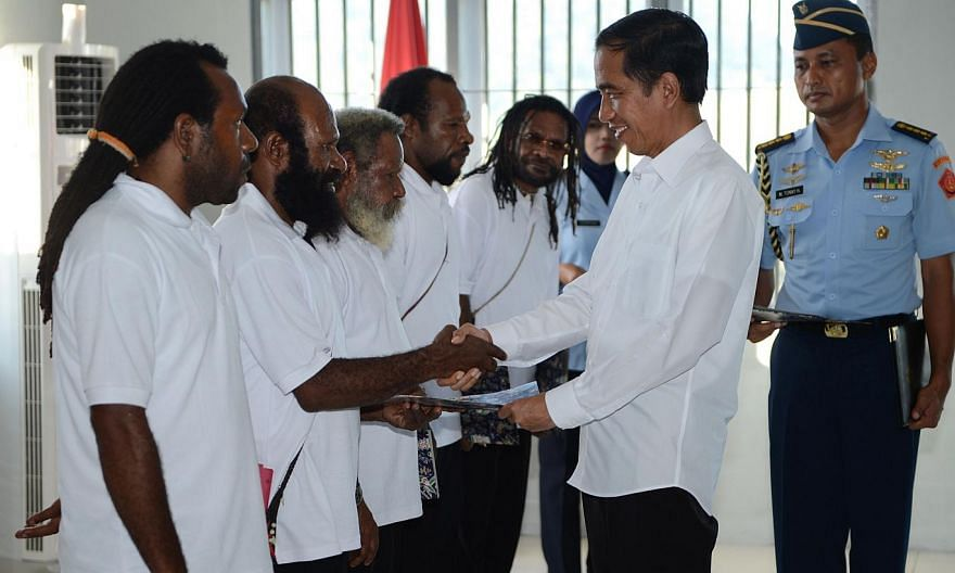 Indonesia's President Joko Widodo (2nd R) shakes hands with freed Papuan political prisoner Kimanus Wenda (2nd L) while four others Jefrai Murib (L) Apotnalogolik Lokobal (3rd L) Numbungga Telenggen (4th L) and Linus Hiluka (3rd R) looks on during a