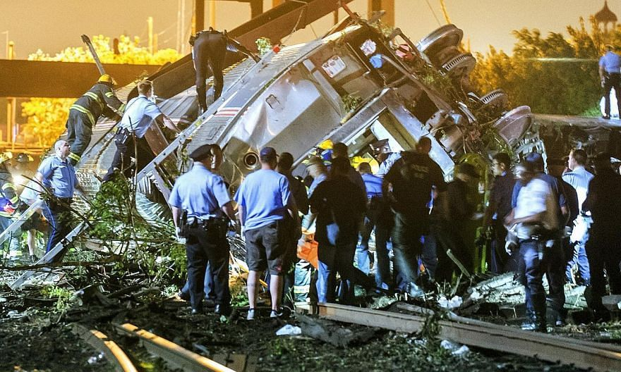 Rescue workers climbing into the wreckage of a crashed Amtrak train in Philadelphia, Pennsylvania on May 12, 2015. -- PHOTO: REUTERS