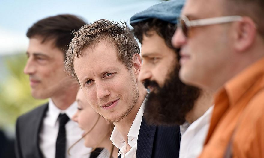 Hungarian director Laszlo Nemes (centre) poses with his cast during a photocall for the film Son of Saul at the 68th Cannes Film Festival on May 15, 2015. -- PHOTO: AFP