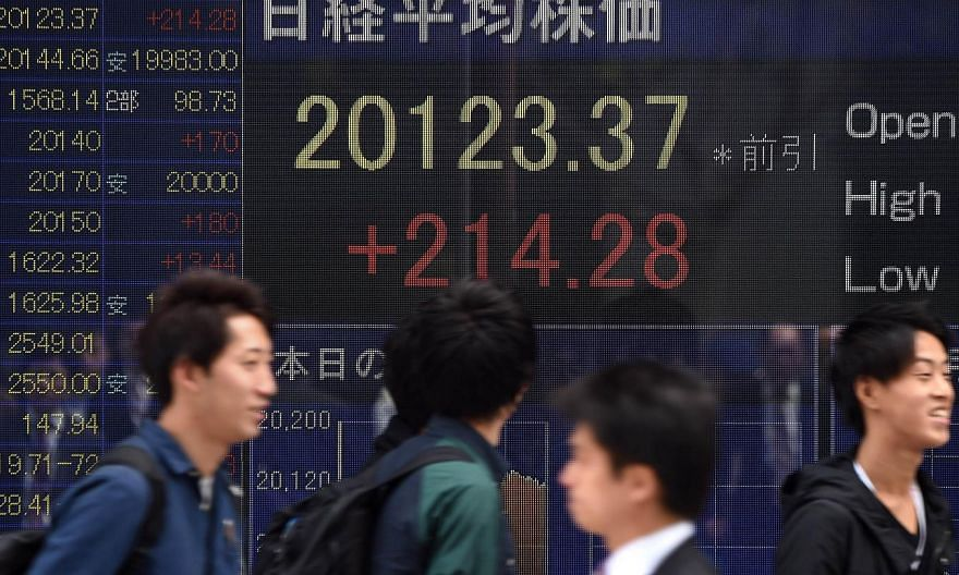 People walking past an electric quotation board flashing the numbers of the Nikkei key index at the Tokyo Stock Exchange (TSE) in front of a securities company in Tokyo. -- PHOTO: AFP