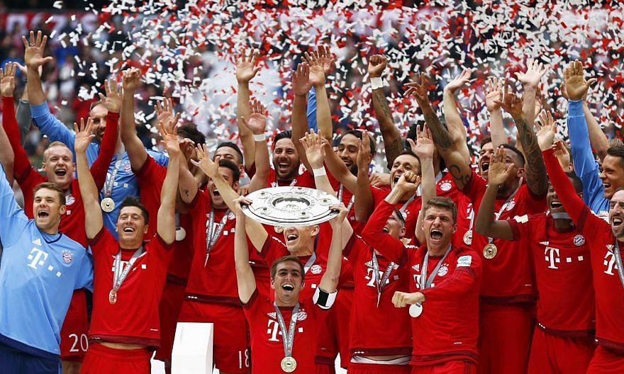 Bayern Munich's Philipp Lahm lifts up the trophy after their final Bundesliga match of the season against Mainz in Munich, on May 23, 2015. -- PHOTO: REUTERS