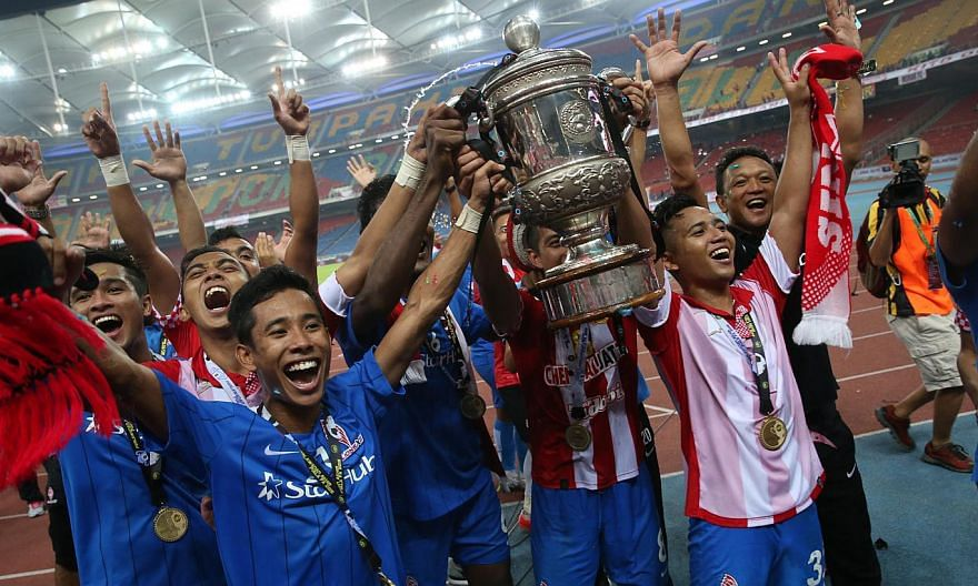 The LionsXII players celebrating with the Malaysian FA Cup after they beat Kelantan 3-1 in the final at Bukit Jalil Stadium on May 23, 2015. -- ST PHOTO: NEO XIAOBIN