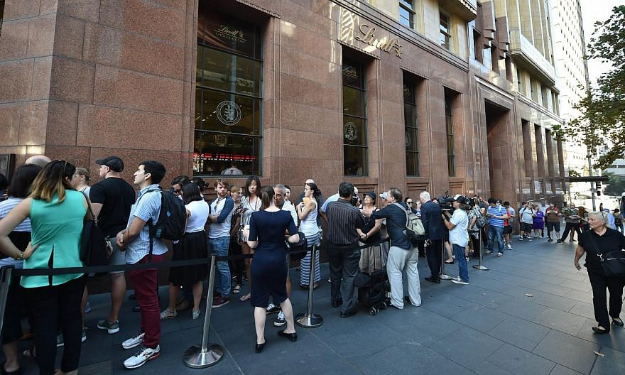 Members of the public queue outside the Lindt Cafe at Martin Place in Sydney ahead of the re-opening on March 20, 2015. Iranian-born Man Haron Monis took more than a dozen customers and staff hostage at the upmarket cafe on Dec 15, an incident which