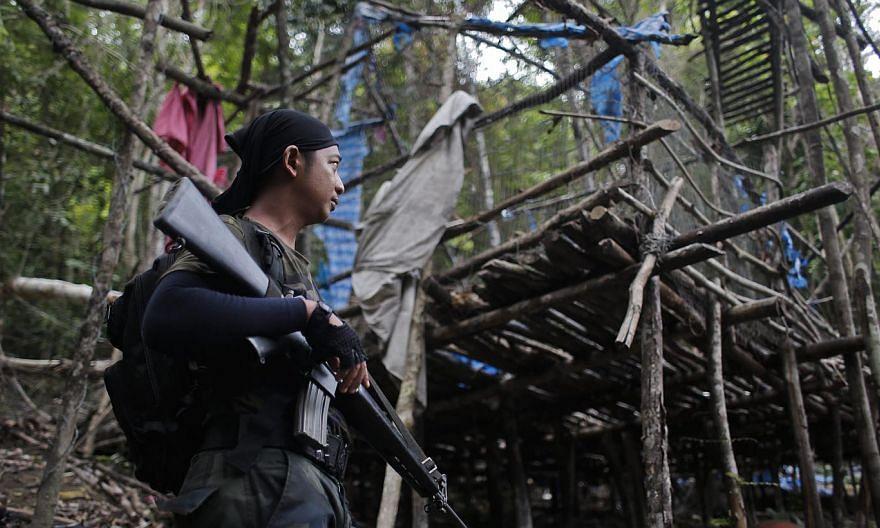 An armed officer from the Royal Malaysia Police standing guard at an abandoned camp at Wang Burma hills in Wang Kelian, Perlis, on May 26, 2015. -- PHOTO: EPA